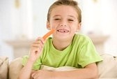 3506645-young-boy-eating-carrot-stick-in-living-room-smiling[1]