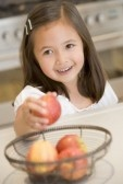 3506792-young-girl-in-kitchen-getting-apple-off-counter-smiling[1]